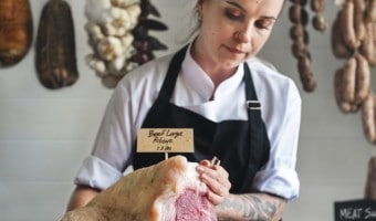 female butcher with beef ribeye
