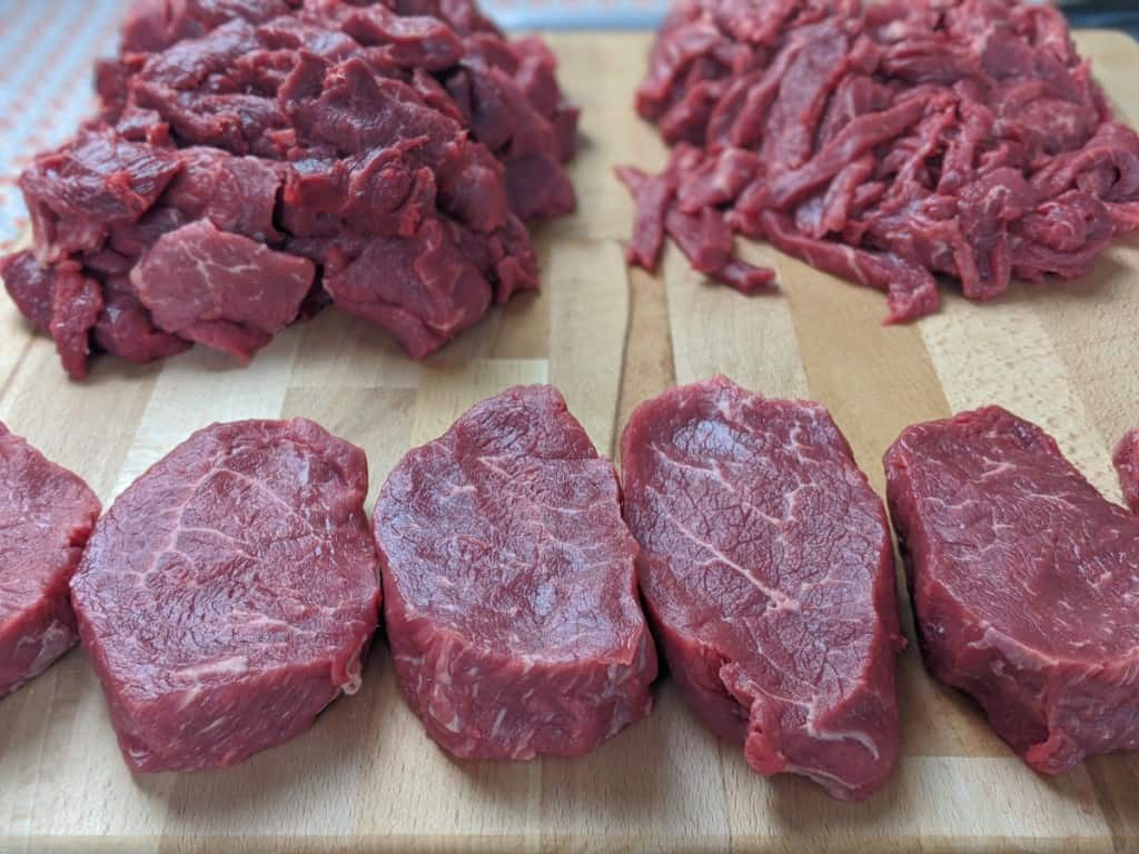 steaks and strips of beef on cutting board