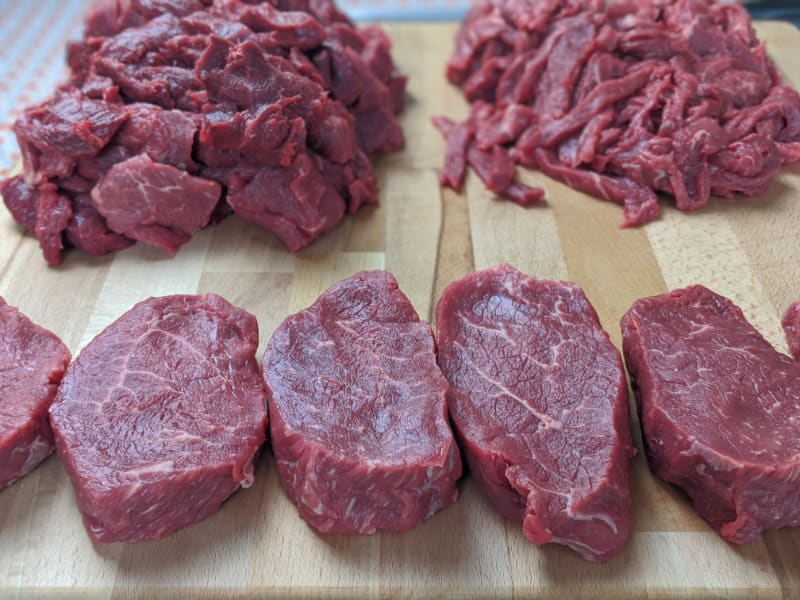 steaks and strips of beef on cutting board 2